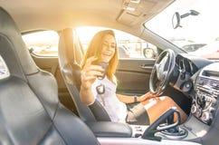 Mujer que muestra las llaves dentro de un coche deportivo foto de archivo