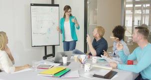 Mujer que muestra los gráficos para los compañeros de trabajo