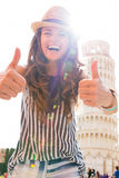 Mujer que muestra los pulgares para arriba delante de la torre de Pisa Foto de archivo libre de regalías