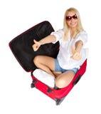Mujer que muestra los pulgares para arriba en maleta del recorrido Foto de archivo libre de regalías