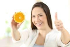Mujer que muestra a medias anaranjado con los pulgares para arriba Imágenes de archivo libres de regalías