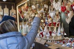 Mujer que muestra a sus amigos alguna decoración de la Navidad en el Chris fotos de archivo libres de regalías