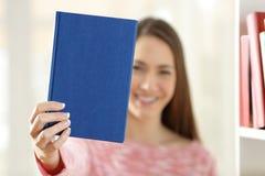 Mujer que muestra una cubierta en blanco de un libro Imagen de archivo