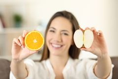Mujer que muestra una naranja y una manzana Imágenes de archivo libres de regalías