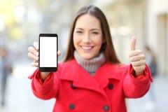 Mujer que muestra una pantalla elegante del teléfono en invierno en una calle Imagenes de archivo