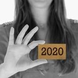 Mujer que muestra una tarjeta de visita - 2020 Imagenes de archivo