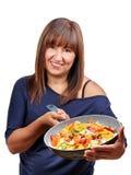 Mujer que muestra verduras de la cacerola Foto de archivo
