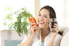 Mujer que muestra zanahorias y el vidrio de agua sanos fotos de archivo libres de regalías
