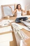 Mujer que mueve adentro - la frustración del ensamblaje de los muebles imagen de archivo libre de regalías
