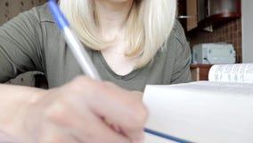 Mujer que mueve de un tir?n a trav?s del libro grande, diccionario y poniendo una cierta informaci?n en escrito, haciendo notas,  almacen de metraje de vídeo