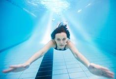 Mujer que nada bajo el agua en piscina Fotografía de archivo
