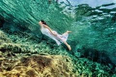 Mujer que nada cerca de roca Foto de archivo libre de regalías