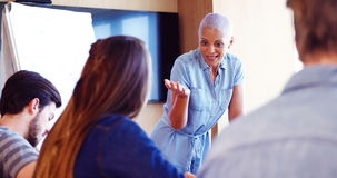 Mujer que obra recíprocamente con sus colegas en la sala de conferencias