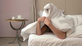 Mujer que oculta bajo la manta almacen de metraje de vídeo