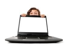 Mujer que oculta detrás de una computadora portátil Imagen de archivo