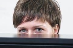 Mujer que oculta detrás del escritorio Imagenes de archivo
