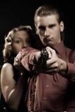 Mujer que oculta detrás del hombre con el arma Imagen de archivo