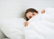 Mujer que oculta detrás de la manta Imagen de archivo libre de regalías