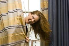 Mujer que oculta detrás de las cortinas Fotos de archivo