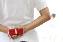 Mujer que oculta el regalo rojo $cox Fotos de archivo