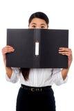Mujer que oculta su cara con un fichero del negocio Foto de archivo