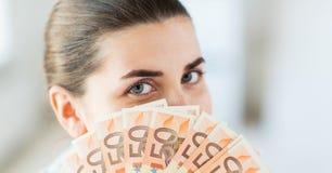 Mujer que oculta su cara detrás de la fan euro del dinero Imágenes de archivo libres de regalías