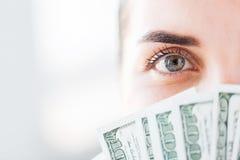 Mujer que oculta su cara detrás de dólar fan del dinero Imágenes de archivo libres de regalías