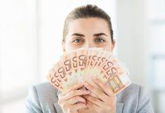 Mujer que oculta su cara detrás de la fan euro del dinero Foto de archivo