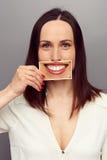 Mujer que oculta sus emociones detrás de la sonrisa Foto de archivo