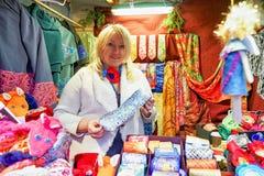 Mujer que ofrece lazos festivos en el mercado de la Navidad de Riga Fotos de archivo