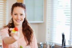 Mujer que ofrece un poco de ensalada Imagen de archivo libre de regalías