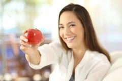 Mujer que ofrece una manzana y que mira la cámara Imagen de archivo libre de regalías