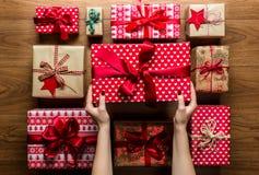 Mujer que organiza los regalos de Navidad maravillosamente desde arriba envueltos del vintage, visión imagen de archivo libre de regalías