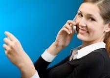 Mujer que paga con de la tarjeta de crédito por el teléfono celular Foto de archivo libre de regalías