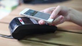 Mujer que paga con el teléfono móvil en el café Primer almacen de metraje de vídeo