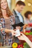 Mujer que paga con la cuenta euro en el supermercado Imagen de archivo