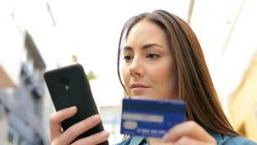 Mujer que paga con la tarjeta de crédito en el teléfono en la calle