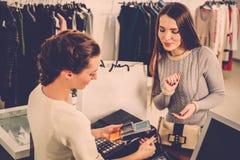 Mujer que paga con la tarjeta de crédito en la sala de exposición de s Imagen de archivo libre de regalías