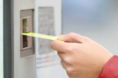 Mujer que paga con la tarjeta de crédito en una máquina del pago Imagen de archivo