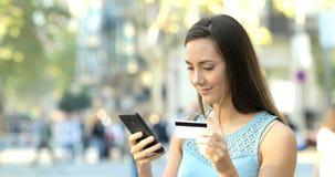 Mujer que paga con la tarjeta y el teléfono de crédito en la calle almacen de metraje de vídeo