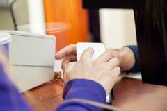 Mujer que paga con Smartphone en la taquilla Imágenes de archivo libres de regalías