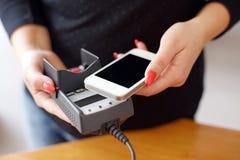 Mujer que paga con tecnología de NFC en el teléfono móvil Foto de archivo libre de regalías