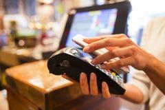 Mujer que paga con tecnología de NFC en el teléfono móvil, restaurante, Ca imágenes de archivo libres de regalías