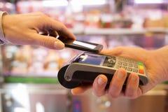 Mujer que paga con tecnología de NFC en el teléfono móvil, en supermercado Fotografía de archivo