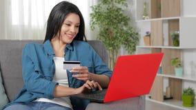 Mujer que paga en línea con la tarjeta de crédito y el ordenador portátil