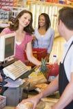 Mujer que paga las tiendas de comestibles Imagen de archivo libre de regalías