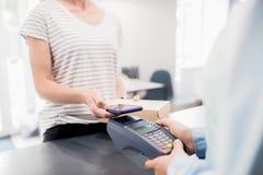 Mujer que paga por Smartphone en tienda fotos de archivo