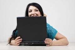 Mujer que parece ausente y espía detrás de la computadora portátil Fotos de archivo libres de regalías