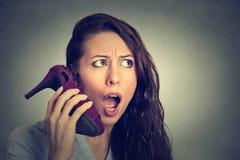 Mujer que parece excitada, sorprendido sosteniendo el zapato de tacón alto en su mano como teléfono Fotos de archivo