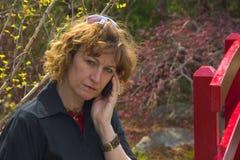 Mujer que parece seria en el teléfono celular Imágenes de archivo libres de regalías